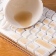 Cup of tea spilled out over a keyboard close up — Stock Photo #25717599