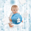 Cute baby holding a blue planet with jigsaw pieces floating arou — Stock Photo