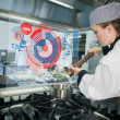 Chief preparing food while consulting futuristic interface — Foto Stock #25717765
