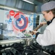 Stock Photo: Chief preparing food while consulting futuristic interface