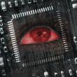 Red eye in middle of black circuit board — Stock Photo