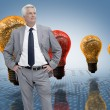 Stock Photo: Businessmin front of colored light bulbs