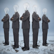 Businessman with bulb head multiplied standing on floor of graph — Stock Photo