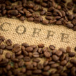 Coffee beans surrounding coffee stamped on sack — Stock fotografie