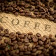 Coffee beans surrounding coffee stamped on sack — Stock Photo #25719063