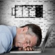Businessman sleeping on his laptop with low battery symbol — Stock Photo