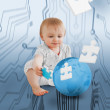 Baby holding jigsaw piece sitingt next to a globe — Stock Photo