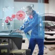 Stock Photo: Mechanic typing while consulting futuristic interface with car d