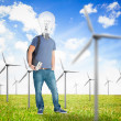 Student with a light bulb head in the middle of wind turbine fie — Stock Photo #25719671