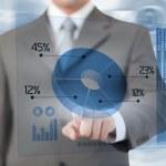 Businessman using blue pie chart futuristic interface — Stock Photo #25719811