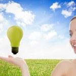Blonde woman presenting green bulb — Stock Photo #25719917