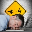 Businessman sleeping on his laptop with battery plug roadsign — Stock Photo #25719945