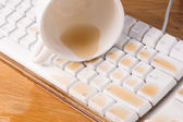 Cup of tea spilled out over a keyboard close up — Stock Photo