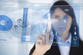 Serious businesswoman using blue pie chart futuristic interface — Stock Photo