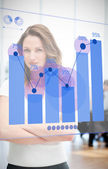 Confident businesswoman looking at blue diagram interface — Stock Photo