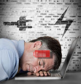 Businessman sleeping on his laptop with low energy and charging — Stock Photo
