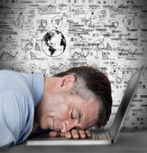 Businessman sleeping on his laptop with drawings and charts — Stock Photo