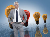 Businessman in front of colored light bulbs — Stock Photo