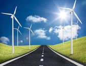 Road leading out to the horizon with wind turbines either side — Stock Photo