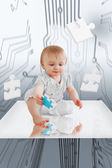 Baby holding jigsaw piece sitting on reflective surface — Stock Photo