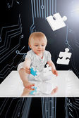 Baby holding jigsaw piece sitting on white reflective surface — Stock Photo