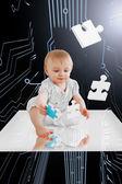 Baby holding jigsaw piece sitting on white reflective surface — Stock Photo