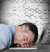 Businessman sleeping on his laptop — Stock Photo