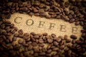 Coffee beans surrounding coffee stamped on sack — Stock Photo