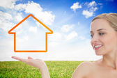 Smiling woman looking at house outline — Stock Photo