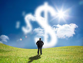 Businessman looking at cloud dollar signs — Stock Photo