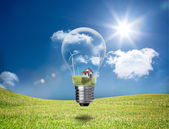 Light bulb showing house and turbines in a field — Stock Photo