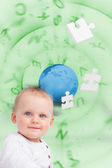 Portrait of a baby with planet and jigsaw pieces green backgroun — Stock Photo