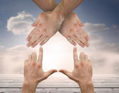 Hands crossed representing a house with blue sky — Stock Photo