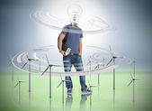 Boy with light bulb for a head surrounded by wind turbines — Stock Photo