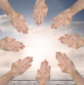 Group of hands forming a circle over blue sky — Stock Photo