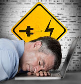 Businessman sleeping on his laptop with battery plug roadsign — Stock Photo