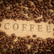 Coffee beans surrounding coffee stamp on sack — Stock Photo #25720157