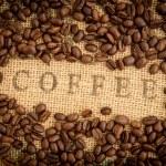 Coffee beans surrounding coffee stamp on sack — Stock Photo