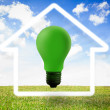 Green light bulb with white house outline - Stockfoto