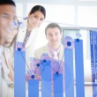 Stock Photo: Smiling business workers looking at blue chart interface