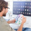 Photo editor looking at colour wheel — Stock Photo