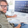 Photo editor turning and smiling at his desk — Stock Photo