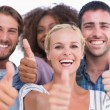 Happy group giving thumbs up — Stockfoto