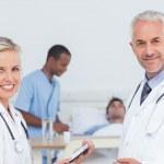 Smiling doctors standing in front of patient — Stock Photo #25724045