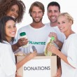 Happy volunteers putting food in donation box — Stock Photo