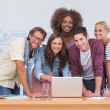 Creative team standing at desk with laptop - Stock Photo