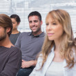 Patients listening in group therapy with one man smiling — Stock Photo