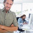 Man smiling in creative office with arms folded — Stock Photo