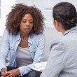 Stock Photo: Patient sitting on sofand talking to therapist