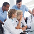 Smiling medical team using laptop — Stock Photo #25726357